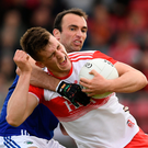 Shane McGuigan of Derry is tackled by Gareth Dillon of Loais. Photo by Ramsey Cardy/Sportsfile
