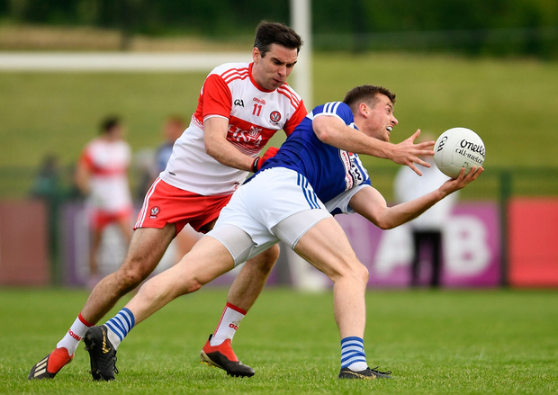 Kieran Lillis of Loais in action against Benny Heron of Derry. Photo by Ramsey Cardy/Sportsfile