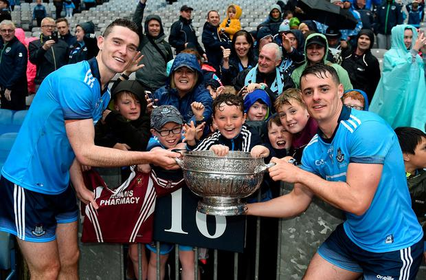 Thrilled: Dublin stars Brian Fenton and Brian Howard of Dublin celebrate with young Raheny club-mates after the match. Photo: Daire Brennan/Sportsfile
