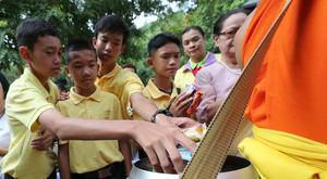 Members of the Wild Boars soccer team who were rescued from a flooded cave, offer foods to a Buddhist monk near the Tham Luang cave in Mae Sai, Chiang Rai province, in Thailand AP Photo/Sakchai Lalit