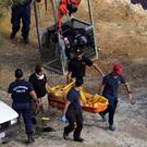 Members of Cyprus Special Disaster Response Unit carry a body retrieved after an investigation for possible bodies of victims of a suspected serial killer in Kokkinopezoula lake near the village of Mitsero in Cyprus REUTERS/Yiannis Kourtoglou/File Photo