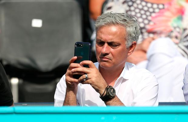 Jose Mourinho takes in the action on his phone during day six of the Fever-Tree Championship at the Queen's Club, London last Saturday. Photo: Steven Paston/PA Wire