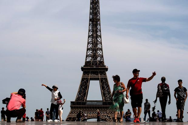 Tourists walk on the Trocadero esplanade with the Eiffel tower in background in Paris on June 24, 2019, as temperatures soar to 33 degrees Celsius. (Photo by Christophe ARCHAMBAULT / AFP)CHRISTOPHE ARCHAMBAULT/AFP/Getty Images