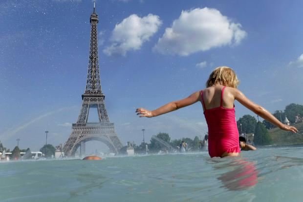 A girl cools off in the fountain of the Trocadero, in Paris, Tuesday, June 25, 2019. (AP Photo/Alessandra Tarantino)