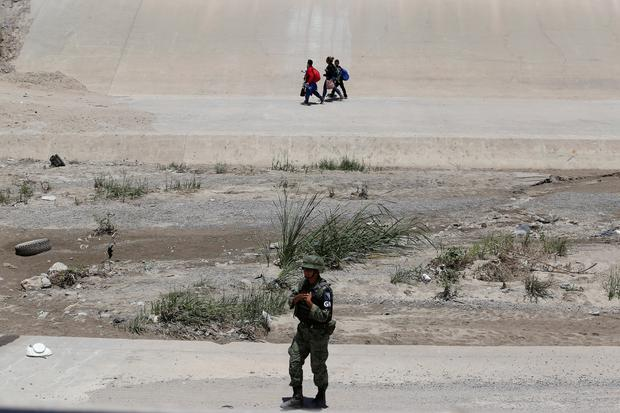 A member of the Mexican National Guard keeps watch as a migrant family walks on the banks of the Rio Bravo river after crossing illegally into El Paso, Texas, United State Picture: REUTERS/Carlos Sanchez Colunga