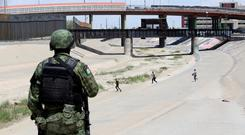 Border crisis: A member of the Mexican National Guard observes migrants running to cross illegally into El Paso, Texas. Photo: REUTERS/Carlos Sanchez Colunga