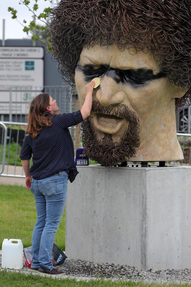 Repair: A graffiti cleaner works on the damage to the Luke Kelly bust on Dublin's Guild Street. Photo: Colin Keegan/Collins
