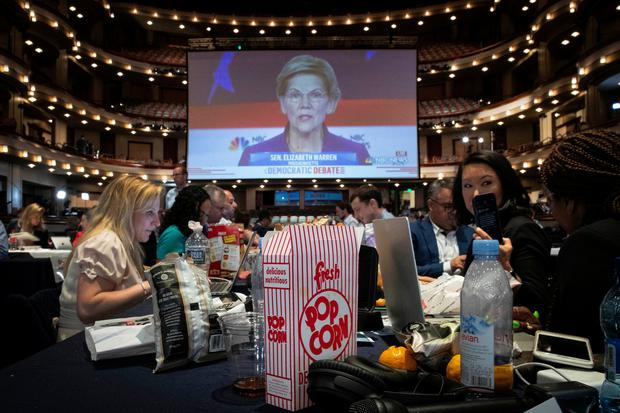 A box of popcorn sits next to reporters as they watch Democratic presidential candidate and U.S. Senator Elizabeth Warrenon a monitor Photo by Drew Angerer/Getty Images