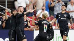 Washington, D.C., USA; D.C. United forward Wayne Rooney (9) celebrates with teammates after scoring a goal from his own half against Orlando City SC at Audi Field. Credit: Geoff Burke-USA TODAY Sports