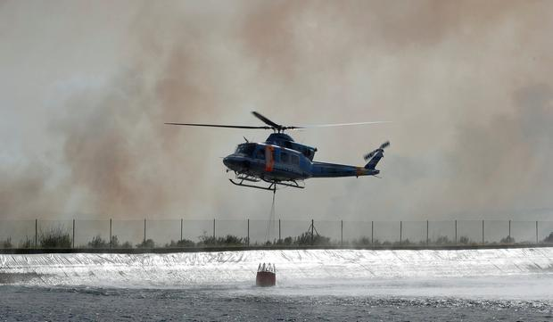 A helicopter reloads water during a forest fire near Bovera, west of Tarragona, Spain, June 27, 2019. REUTERS/Albert Gea