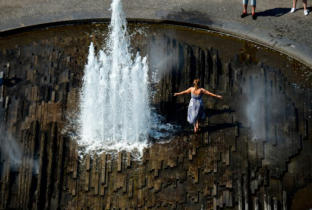 A woman cools off in a water fountain on June 26, 2019 at the Lustgarten in central Berli. Photo by Tobias SCHWARZ / AFP
