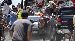 People fly into the air as a vehicle is driven into a group of protesters (Ryan M. Kelly/AP)