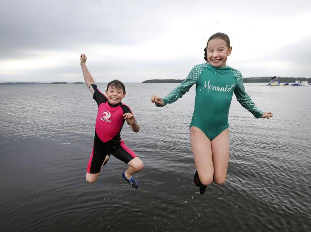 Hazel Ryan (11) and her brother Diarmuid (9), from Ballybricken, Co Limerick, leap into Lough Derg at Dromineer, Co Tipperary. Photo: Damien Eagers / INM