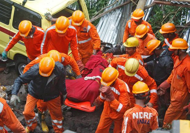 Rescue workers carry the body of a victim at the site of a collapsed wall of a residential complex in Pune, India, June 29, 2019. REUTERS/Stringer