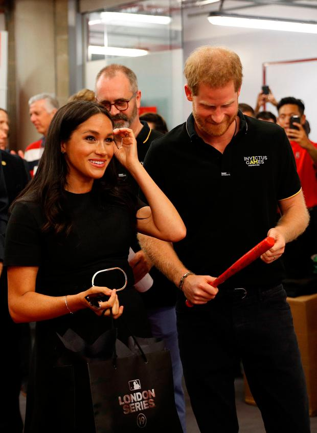 The Duke and Duchess of Sussex receive presents for their son Archie as they meet players of the Boston Red Sox as they attend the Boston Red Sox vs New York Yankees baseball game at the London Stadium in support of the Invictus Games Foundation