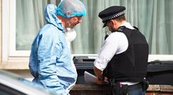 A forensic officer speaks with a police officer at the scene in Raymead Avenue, Thornton Heath, Croydon where a women who was around eight months pregnant was stabbed to death. Kirsty O'Connor/PA Wire