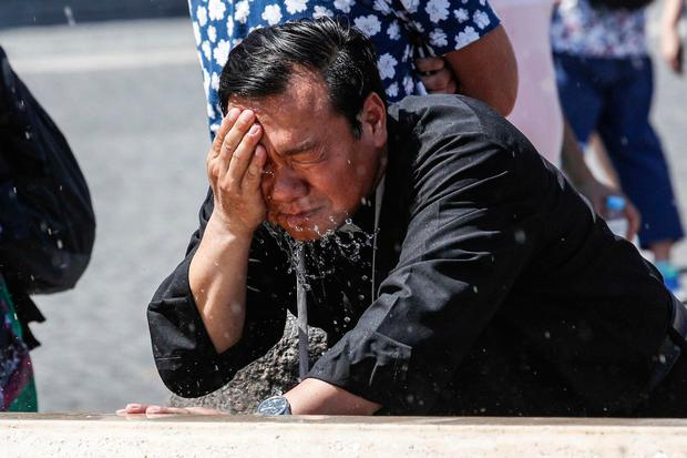 A priest cool-offs in the fountain of St. Peter Square at the Vatican. (Giuseppe Lami/ANSA via AP)
