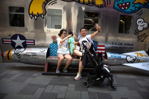 Two nations in talks: A family poses for a selfie while sitting on a bench shaped like a missile painted with the US flag outside of a clothing store at a shopping mall in Beijing. AP Photo/Mark Schiefelbein