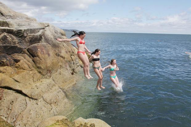 Isabel Coghlan, Izzy Behanbeer and Alana Carvill leap into the Forty Foot at Sandycove in Dublin. Photo: Stephen Collins/Collins Photos