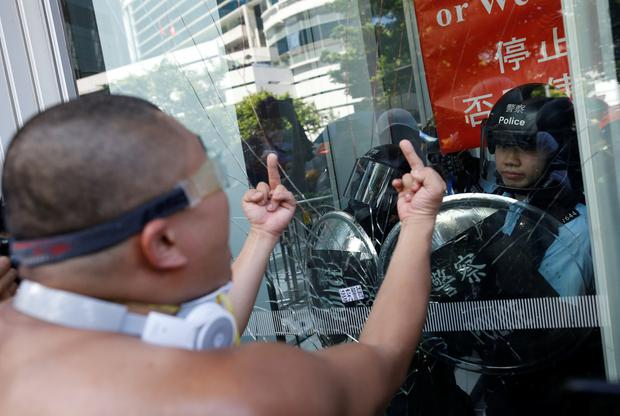 Protester gestures as he tries to break into the Legislative Council building where riot police are seen, during the anniversary of Hong Kong's handover to China in Hong Kong, China July 1, 2019. REUTERS/Thomas Peter