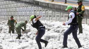 Security forces and soldiers try to clear away ice after a heavy storm of rain and hail which affected some areas of the city in Guadalajara, Mexico. Picture: REUTERS/Fernando Carranza
