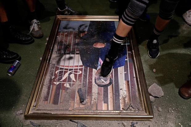 A protester steps on a damaged portrait of former legislative leader lie on the ground after protesters broke into the Legislative Council building in Hong Kong. Picture: AP Photo/Vincent Yu