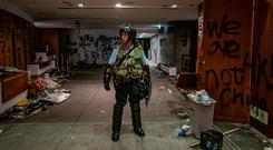 A riot police stands near graffiti inside the Legislative Council building after it was damaged by demonstrators during a protest. Photo by Anthony Kwan/Getty Images