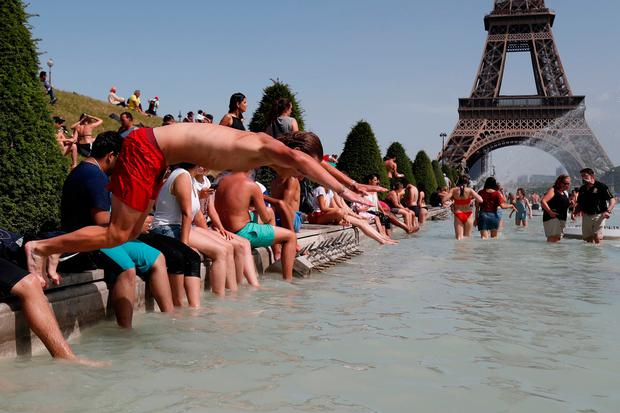 Cooling down: A boy jumps into the water of the Trocadero Fountain in Paris during last month's heat wave. Photo: AFP/Getty Images