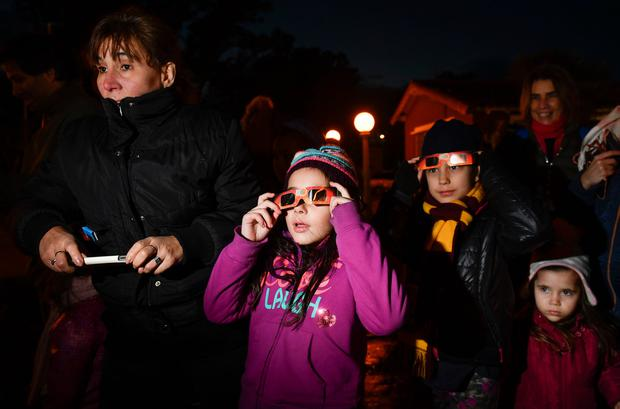 People stand in the dark as they stop to view a total solar eclipse in Chascomus, Argentina, Tuesday, July 2, 2019. A solar eclipse occurs when the moon passes between the Earth and the sun and scores a bull's-eye by completely blocking out the sunlight. (AP Photo/Gustavo Garello)
