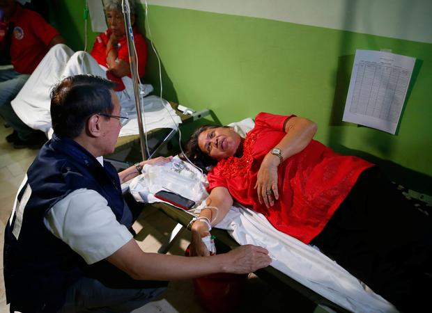 Philippine Health Secretary Francisco Duque III talks to patients who fell ill during the 90th birthday celebration of former Philippine First Lady Imelda Marcos. Picture: AP Photo/Bullit Marquez