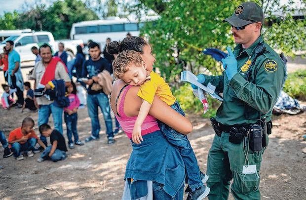 Exhausting process: A US border patrol agent takes down information from Ana Esmeralda, from El Salvador, and her son Manuel Alexander, (2) after they were taken into custody. Photo: John Moore/Getty Images