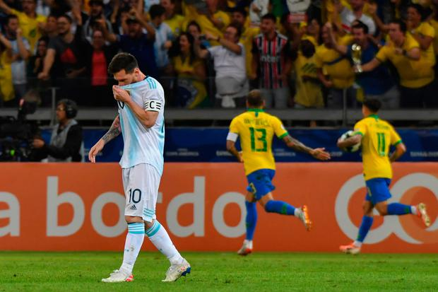 Argentina's Lionel Messi looks dejected as Brazilian players celebrate the goal by teammate Gabriel Jesus during the Copa America semi-final