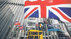 Making a mark: British flags flutter next to protest placards placed by protesters outside the Central Government Office building in Hong Kong. Photo: Andy Wong/AP
