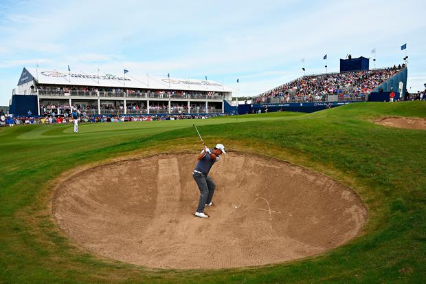 Closing it out: Padraig Harrington plays his third shot from the greenside bunker on the 18th on his way to recording a birdie. Photo: Getty