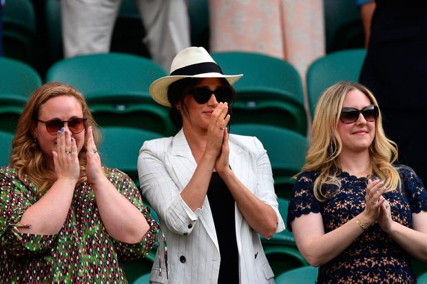 Britain's Meghan (C), Duchess of Sussex applauds after US player Serena Williams beat Slovakia's Kaja Juvan during their women's singles second round match on the fourth day of the 2019 Wimbledon Championships at The All England Lawn Tennis Club in Wimbledon, southwest London, on July 4, 2019. (Photo by Glyn KIRK / AFP)