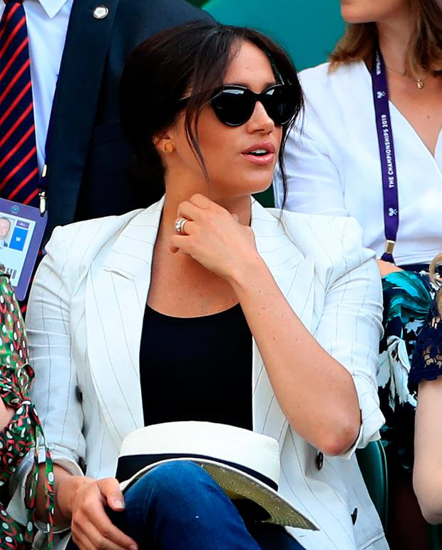 Duchess of Sussex watches Serena Williams on court one on day four of the Wimbledon Championships at the All England Lawn Tennis and Croquet Club, Wimbledon