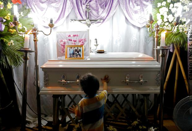 The brother of 3-year-old Myca Ulpina wipes her casket during her wake in Rodriguez, Rizal province, Philippines. Picture: REUTERS/Eloisa Lopez