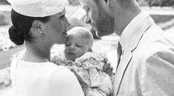 In this official christening photograph supplied by the Duke and Duchess of Sussex, Prince Harry, Duke of Sussex and Meghan, Duchess of Sussex pose with their son, Archie Mountbatten-Windsor with the Rose Garden in the background at Windsor Castle on July 06, 2019 in Windsor, United Kingdom. (Photo by Chris Allerton/SussexRoyal)