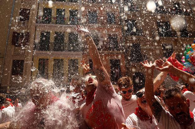 Revellers cool off with water thrown from a balcony during the opening of the San Fermin festival in Pamplona, Spain, July 6, 2019. REUTERS/Susana Vera