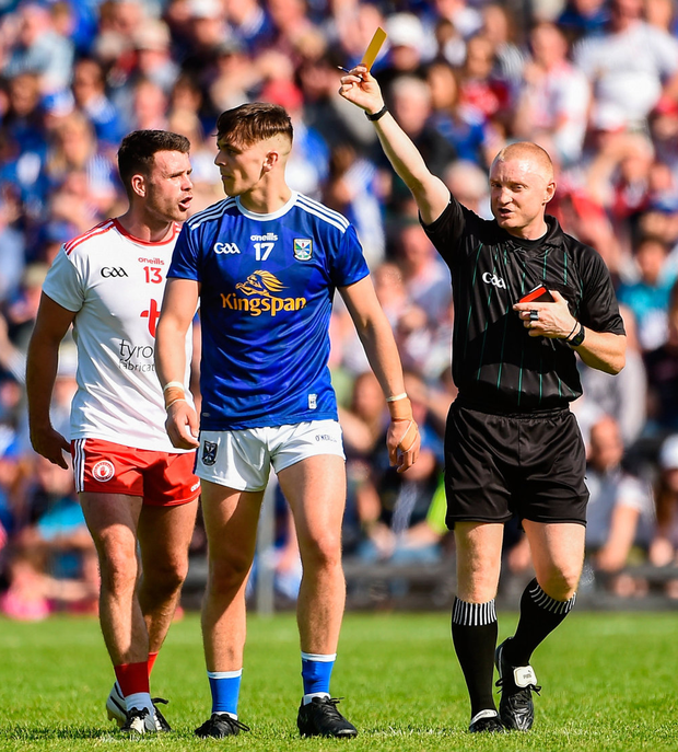 Tyrone's Darren McCurry and Cavan's Barry Fortune are both issued with yellow cards by Referee Barry Cassidy. Photo: Oliver McVeigh/Sportsfile