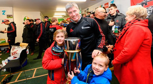 Assistant coach Ronan O'Gara of the Crusaders and his children pose with the Super Rugby trophy in the changing room after winning the final against the Jaguares. Photo: Getty