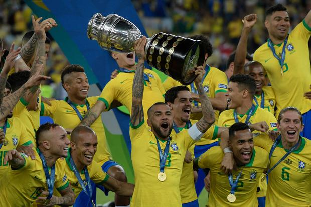 Brazil's Dani Alves (C) and teammates celebrates with the trophy after winning the Copa America after defeating Peru. Photo: JUAN MABROMATA/AFP/Getty Images