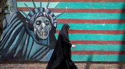Tensions: A woman walks in front of a mural depicting the Statue of Liberty in Tehran, Iran. Photo: Nazanin Tabatabaee/ WANA (West Asia News Agency) via REUTERS