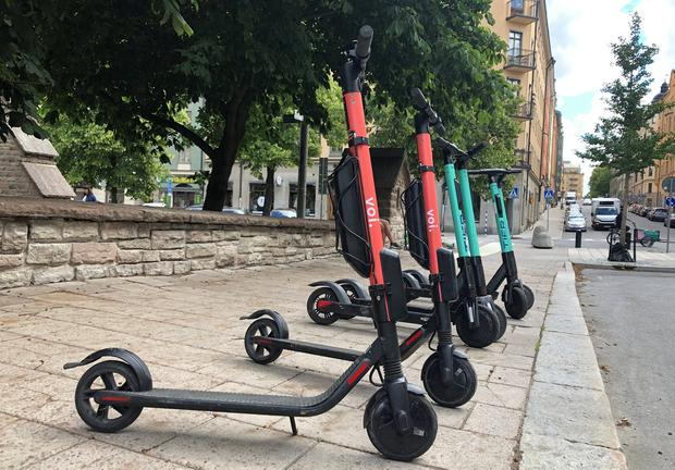 Electric scooters from Swedish startup VOI and Belin-based Tier sit parked side-by-side in Stockholm, Sweden. Photo: Reuters