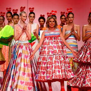 Spanish designer Agatha Ruiz De La Prada (C) acknowledges the audience after presenting creations from the Spring/Summer 2020 collection during the Mercedes Benz Fashion Week in Madrid on July 8, 2019. (Photo by GABRIEL BOUYS / AFP)