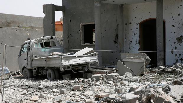 A vehicle and structure is damaged from fighting in the region of Tajoura, east of the Libyan capital Tripoli. AP Photo/Hamza Turkia, File