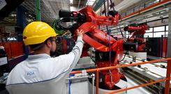 A Mirafiori FCA worker is seen during the installation of the first robot on the production line for the new electric Fiat 500 BEV at the Mirafiori industrial complex. Photo: REUTERS/Massimo Pinca