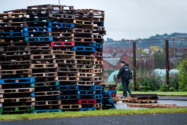 Two PSNI officers walking towards the 11th night bonfire at Avoniel Leisure Centre, after a statement was read out by a Belfast City Council worker from inside a PSNI vehicle requesting that people on council property vacate the area. Belfast City Council reaffirmed its decision yesterday for the third time, to remove materials from a bonfire site beside the centre. Liam McBurney/PA Wire