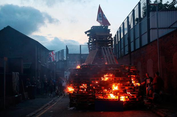 People attend an 11th night Bonfire in Cluan Place, Belfast, as hundreds of bonfires were set to be lit at midnight, as part of a loyalist tradition to mark the anniversary of the Protestant King William's victory over the Catholic King James at the Battle of the Boyne in 1690. Brian Lawless/PA Wire