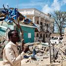 A man passes in front of the rubbles of the popular Medina hotel of Kismayo (Photo by - / AFP)-/AFP/Getty Images